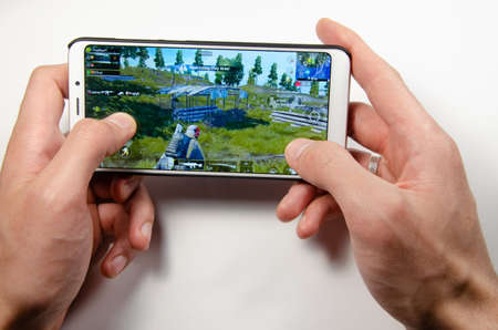 Photo for April, 2019. Kramatorsk, Ukraine. The gameplay of the game PUBG G Mobile on a white smartphone in hand - Royalty Free Image