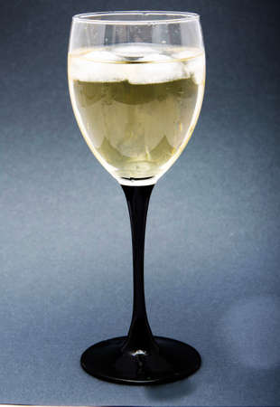 Photo pour A glass of white wine with pieces, ice cubes. Wine with ice on a black background. Glass with a black leg - image libre de droit