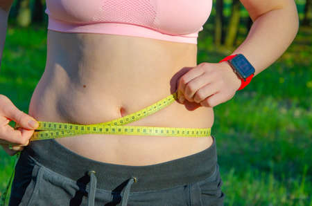 Photo for The girl measures her waist, a whirlpool with a yellow centimeter. Fat belly, folds of fat. Sports, proper nutrition, weight loss. - Royalty Free Image