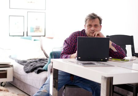 Photo for middle-aged man working remotely at home office - Royalty Free Image