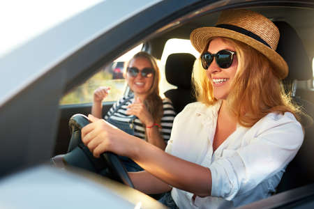 Photo for Two young cheerful smiling women in a car on vacation trip to the sea beach. Girl in glasses driving a vehicle from rental on holidays. Girlfriends enjoying summer arrived to ocean shore on holidays. - Royalty Free Image