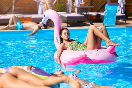 Photo pour Young hot girl in bikini relaxing and chilling on inflatable pink flamingo pool float. Pretty tanned woman in swimsuit lies in the sun on tropical vacation. Pretty female sunbathing at luxury resort. - image libre de droit