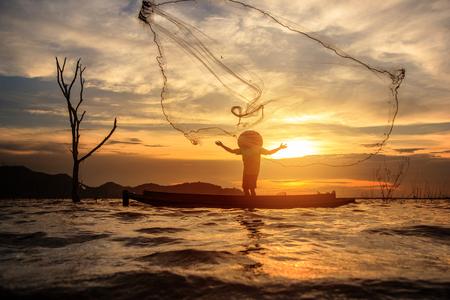 Photo pour Fisherman catch fish by his fishing net during sunset. - image libre de droit