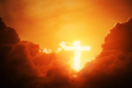 Foto de Conceptual wood cross or religion symbol shape over a sunset sky with clouds background for God. belief or resurrection of god and worship christian. - Imagen libre de derechos