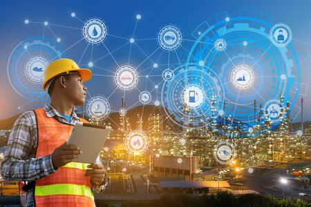 Photo pour businessman hands hold tablet working with night oil refinery industry plant and industry icons. Factory in the night as communication of energy. Smart technology 4.0 and communication - image libre de droit