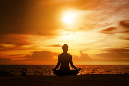 Photo pour woman practicing yoga during surrealistic sunset at the seaside. healthy concept and workout. - image libre de droit
