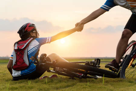 Photo pour Woman riding mountain bike was accident crashed and fell to the grass while a lover her coming in to help at the beautiful sunset time. Using help and giving family love concept. - image libre de droit