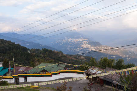 Gangtok mountain village with green trees, blue sky and wire that view form upper level of Rumtek Monastery in winter near Gangtok. Sikkim, India.