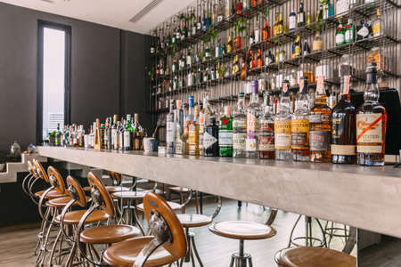 Photo pour Concrete counter bar with mirror below with many brands liquors on the top and back shelf. - image libre de droit