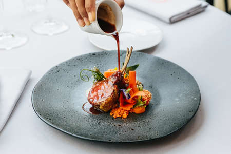 Photo for Modern French cuisine: Roasted Lamb neck & rack served with carrot, yellow curry and lamb sauce. Served in black stone plate with fork and knife. - Royalty Free Image