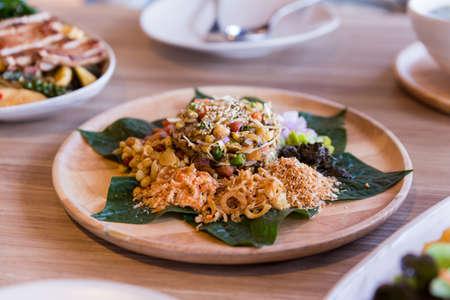 Foto de Lahpet is Burmese Tea Leaf Salad served with deep fried garlic, peanut, white sesame, dried shrimp, ginger and roasted coconut. - Imagen libre de derechos