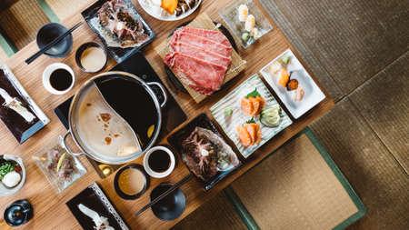 Foto de Top view of Shabu set including rare slices Wagyu A5 beef, Shabu shoyu and clear base, salmon, sushi and vegetables. - Imagen libre de derechos