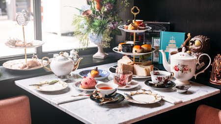 Photo pour English afternoon tea set including hot tea, pastry, scones, sandwiches and mini pies on marble top table. - image libre de droit