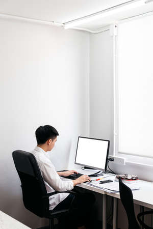 Photo pour Back of the man wearing white shirt and sit on black office chair, working with his personal computer with display on office table. - image libre de droit