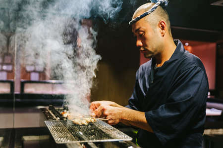 Photo for Japanese Yakitori Chef is grilling chicken marinated with ginger, garlic and soy sauce with a lot of smoke. - Royalty Free Image