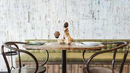Photo for Dining area decorated with green sofa, wooden top table, black steel chair and white scratch texture wallpaper. Modern interior restaurant atmosphere. - Royalty Free Image