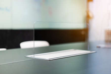 Foto de Close up of acrylic  separator standing partition wall with pass-through on the desk in the meeting room. Social distancing in offices during the Covid-19 pandemic. Precaution and safe. - Imagen libre de derechos
