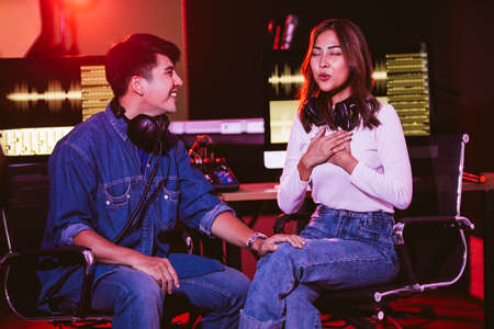 Photo pour A pretty Asian female tries to sing with her producer in the studio in a rehearsal session. Performance and show in the music business. Image with copy space. Small and home recording studio. - image libre de droit