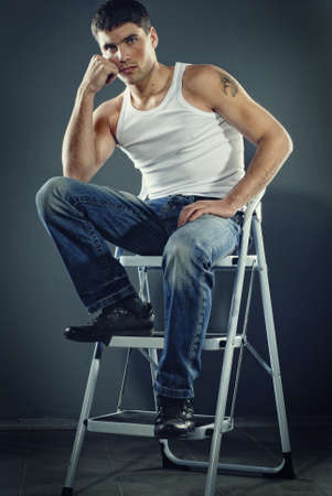attractive man in jeans sitting on stairs