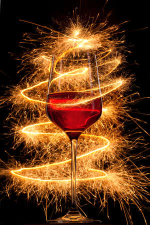 Photo for Wine in glass with burning sparklers on black background - Royalty Free Image