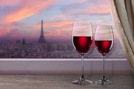 Photo pour View of Paris and Eiffel tower on sunset from window with two glasses of wine - image libre de droit