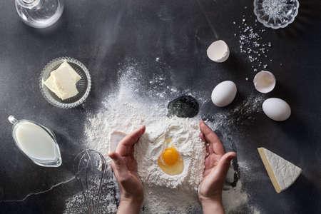 Woman hands knead dough on table with flour