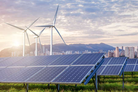 Photo for solar panels and wind turbines under sky and clouds with city on horizon. Sunrise - Royalty Free Image