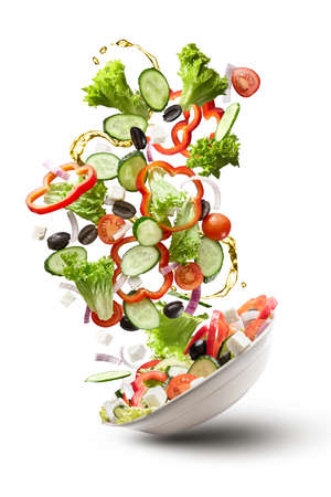 Foto de flying salad isolated on white background. Greek salad: red tomatoes, pepper, cheese, lettuce, cucumber, olives and olive oil - Imagen libre de derechos