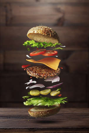 Photo pour Classic burger ingredients flying on a wooden brown background - image libre de droit