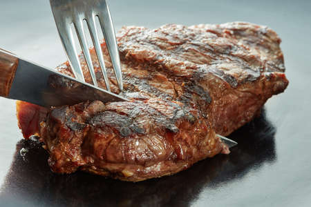 piece of steak cut with a fork and knife on dark background