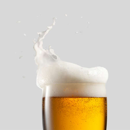 Photo pour Close-up of cold beer with foam and splash on a gray background - image libre de droit