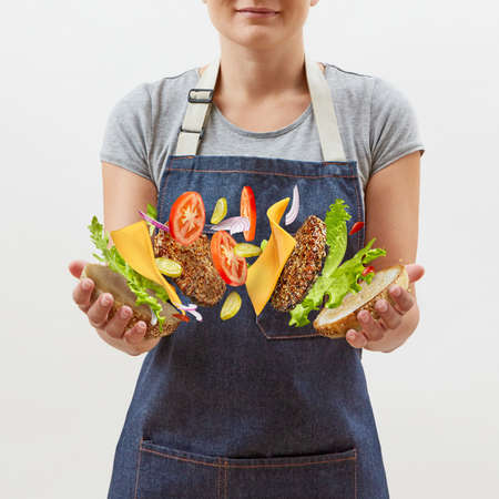 Photo pour Female chef in a denim apron with flying tasty homemade burger from fresh natural ingredients in her hands on a white background. Place for text. - image libre de droit