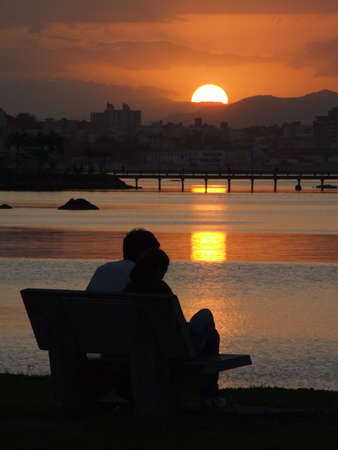 Young couple contemplating the sunset in Florianopolis - Santa Catarina - Brazil