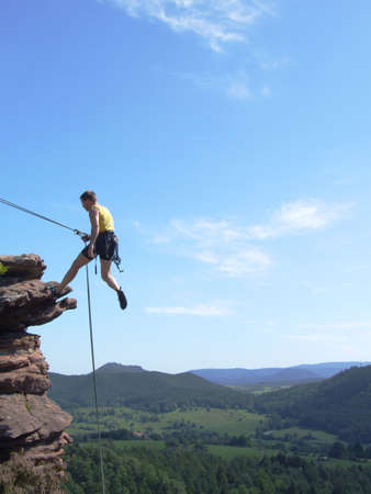 Free climber with rope against blue sky in Palatinate - Germany