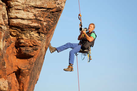 Photo for Photographer and rock climber Norbert Frank taking pictures in while hanging in front of a rock - Royalty Free Image