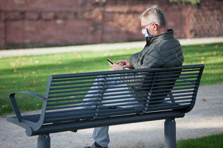Photo for Mature man with face mask looking at a mobile phone while sitting on a park bench - selective focus on the head and hand - Royalty Free Image