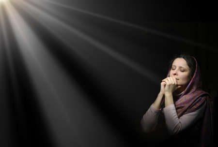 Photo for Dramatic evangelical pentecostal pious kneeling grieve young white lady cover head for ask implore wish upwards Jesus Christ. Vintage repentance concept copyspace with space for text on dark backdrop - Royalty Free Image