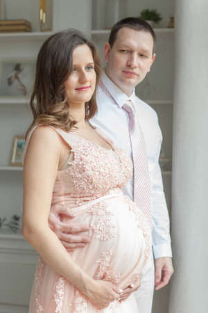 Portrait of lovely future parents at home. Pregnancy, maternity, preparation and expectation concept