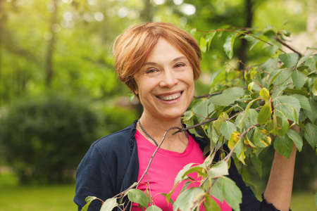 Foto de Healthy mature woman having fun with green leaves outdoor. Beautiful model 60 years old - Imagen libre de derechos