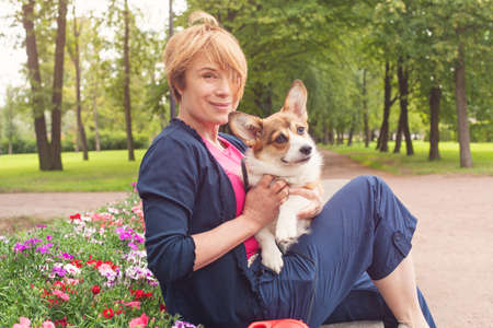 Photo pour Happy elderly woman sitting with dog on bench in blossom summer park - image libre de droit