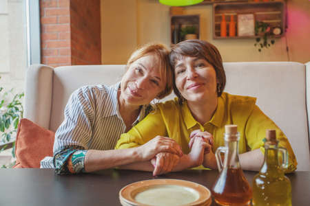 Photo pour Attractive mature mother and daughter eating and chatting in restaurant - image libre de droit