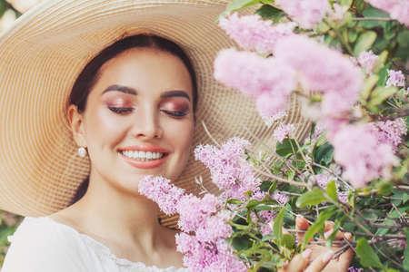 Photo pour Elegant young woman in white hat with flowers outdoor - image libre de droit