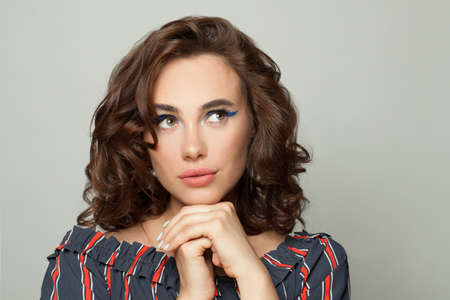 Photo pour Attractive woman with brown curly bob hairdo looking up aside on white - image libre de droit