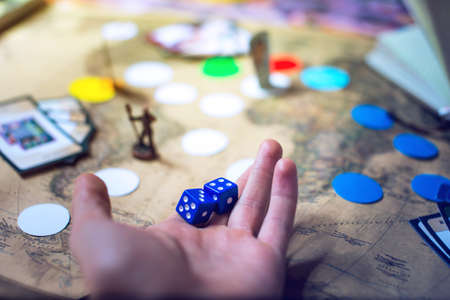 Foto de hand throws the dice on the background blurred colorful fantasy world map Board games, gaming moments in dynamics - Imagen libre de derechos