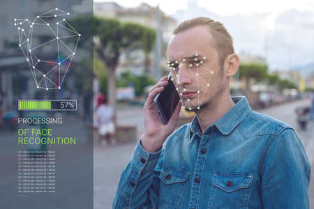 Foto de Biometric verification. Modern young man with the phone. The concept of a new technology of face recognition on polygonal grid is constructed by the points of IT security and protection - Imagen libre de derechos