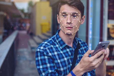 Photo for Biometric verification. Modern young man with the phone. The concept of a new technology of face recognition on polygonal grid is constructed by the points of IT security and protection - Royalty Free Image