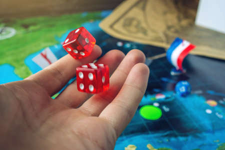 Photo pour Hand throwing red dice on the world map of the playing field handmade Board games with a pirate ship. The game of battleship. - image libre de droit
