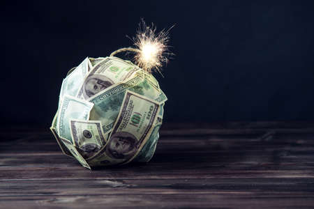 Photo pour Big bomb of money hundred dollar bills with a burning wick. Little time before the explosion. The concept of financial crisis - image libre de droit