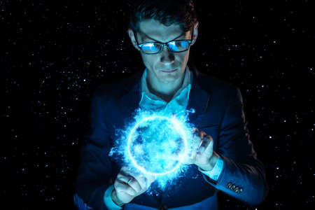 Photo pour A man businessman holding hands over a blue glowing plasma sphere. Magic prediction and foresight in business and Finance - image libre de droit