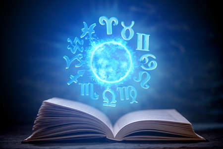Photo for Open book on astrology on a dark background. The glowing magical globe with signs of the zodiac in the blue light. Prediction and magic - Royalty Free Image
